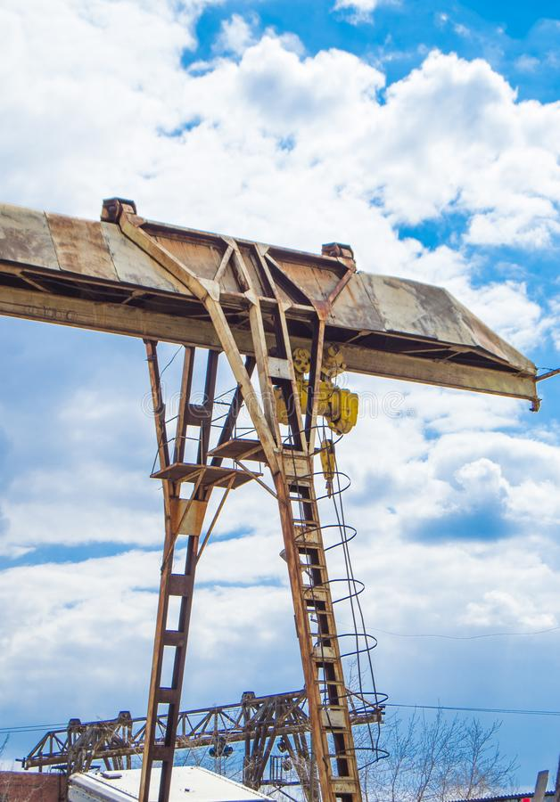 Old rusty gantry crane on blue sky background, vertical shot, outdoors.  stock photos