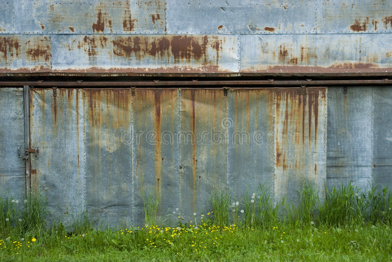 Old Rusty Garage Doors. Rusty locked garage doors overgrown by grass and weeds royalty free stock images
