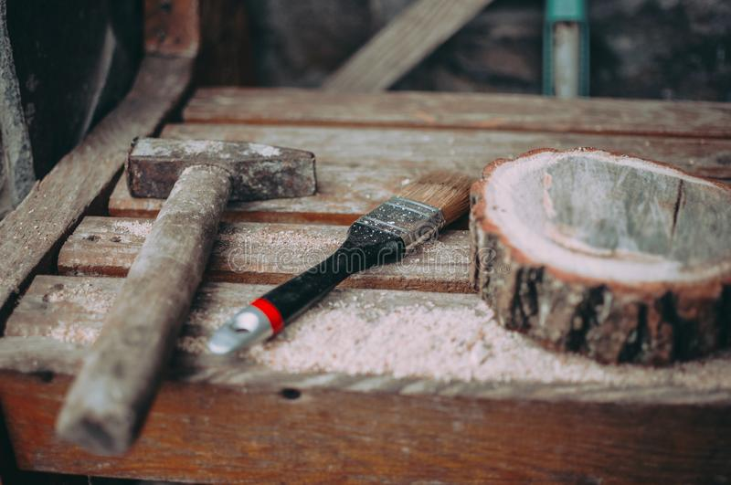 An old rusty hammer, a paint brush and a round pine beam with sawdust on a bench. Wooden stand for food for the master class. DIY royalty free stock photo