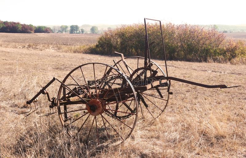 Old rusty hay turner on a field. Old rusty hay turner standing on a dry field in sunlight royalty free stock photo