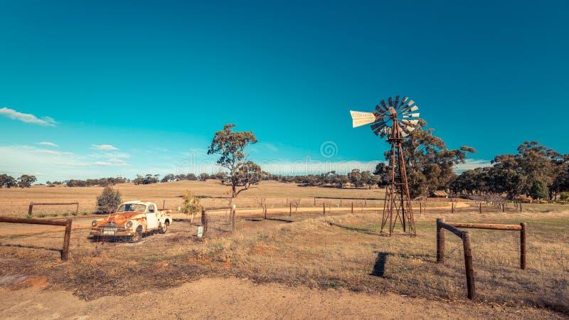 Old rusty Holden FJ Ute and Kookaroo windmill stock photos