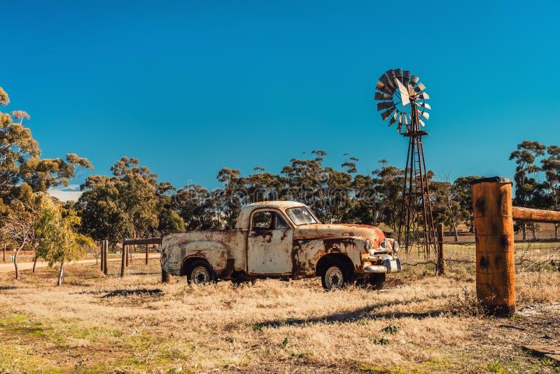 Old rusty Holden FJ Ute and Kookaroo windmill stock photo