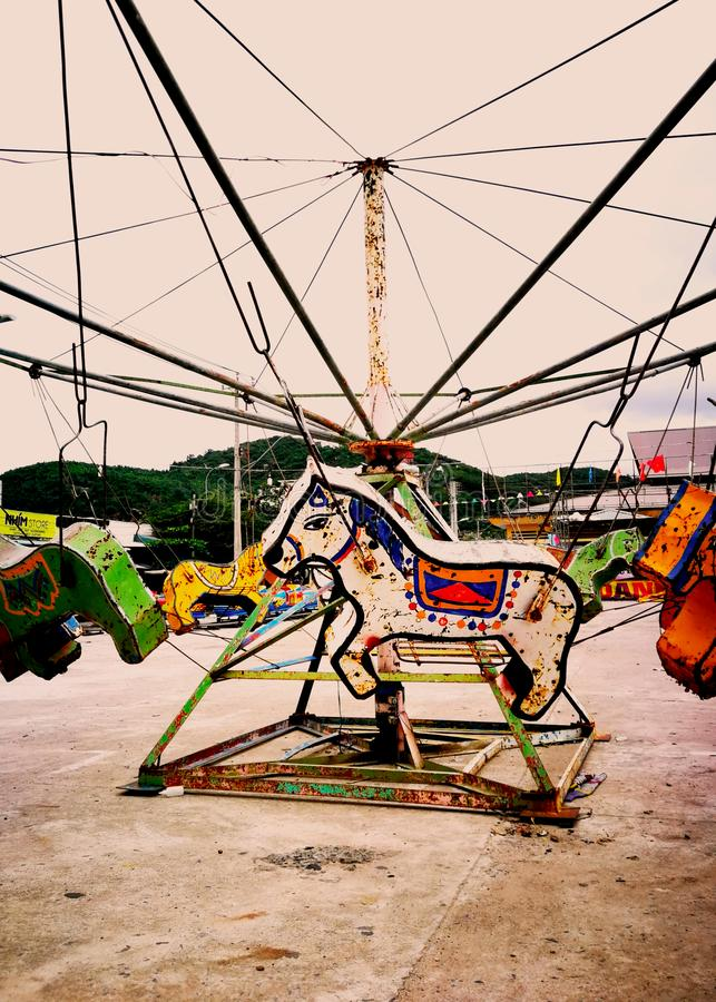 An old rusty horse carousel in an abandoned amusement Park . stock photos