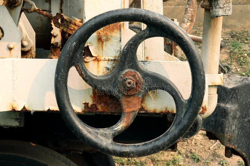 Old and rusty industrial pipe valve at power plant, Metalworking industry : gear wheel machine royalty free stock photography