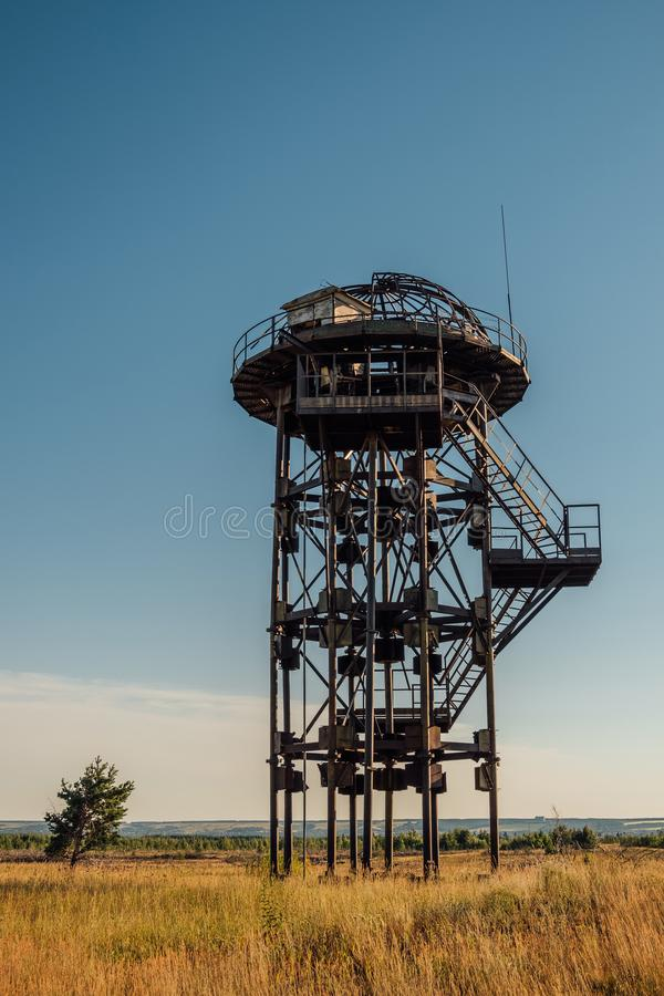 Old rusty iron abandoned watch tower in wastelands. Post-apocalyptic concept royalty free stock photography