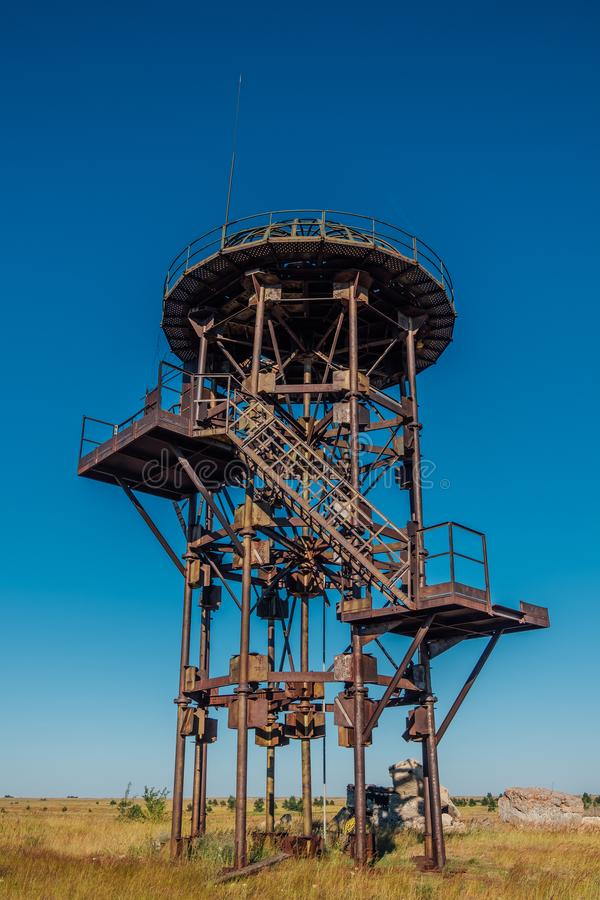 Old rusty iron abandoned watch tower in wastelands. Post-apocalyptic concept royalty free stock photo