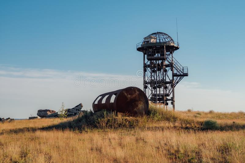 Old rusty iron abandoned watch tower in wastelands. Post-apocalyptic concept royalty free stock images