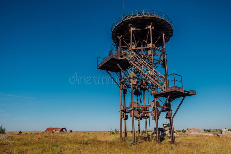 Old rusty iron abandoned watch tower in wastelands. Post-apocalyptic concept royalty free stock image