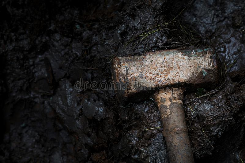 Old rusty iron construction hammer on the mud, dramatic photography and low key photography. construction tool and crime concept stock images