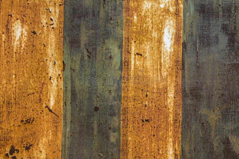 Old rusty iron metal sheet with peeling yellow and blue paint. vertical stripes. rough surface texture stock photos