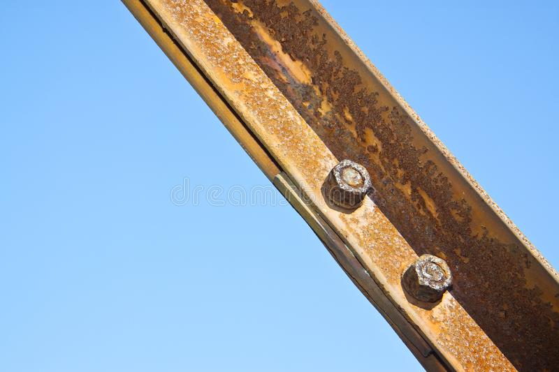 Old rusty iron structure with bolted metal profiles against a blue sky stock photos