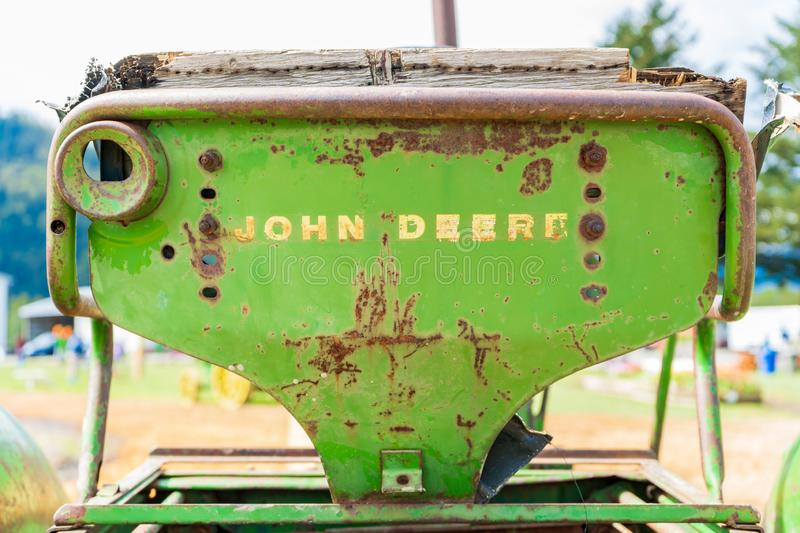 Old, rusty John Deere tractor seat, showing the word mark logo on the back, worn out. Classic John Deere image of an antiquated stock image
