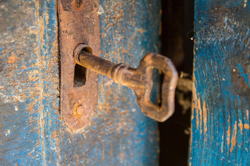 Old rusty key and keyhole on a blue wooden door royalty free stock photos