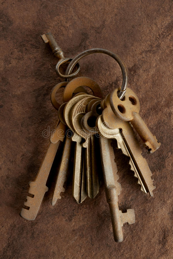 Old rusty keys. Several old rusty keys on ring shot on textured background stock photos
