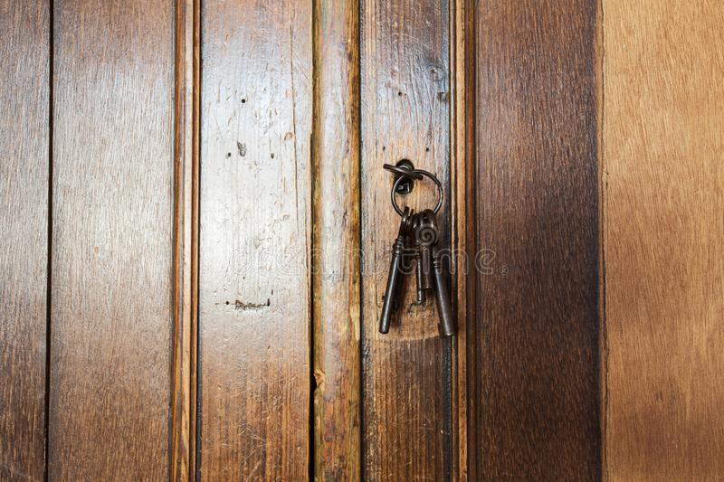Old rusty keys inside a keyhole of an old antique closet. vintage design. Close-up stock photography