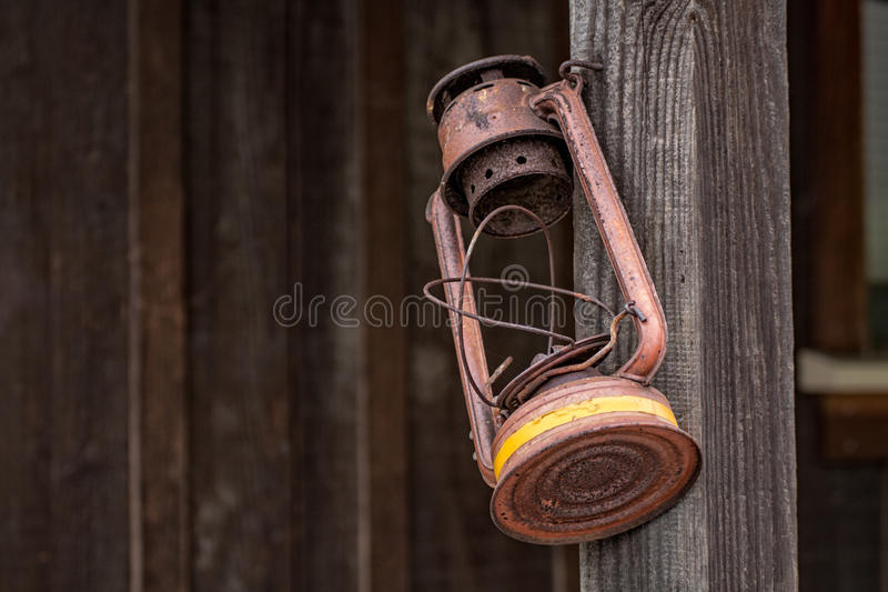 Old,rusty lamp hanging on post stock photo