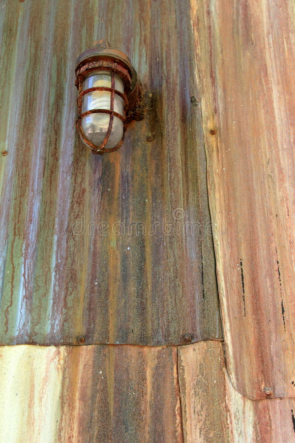 Old rusty lantern hanging on weathered metal siding royalty free stock photo