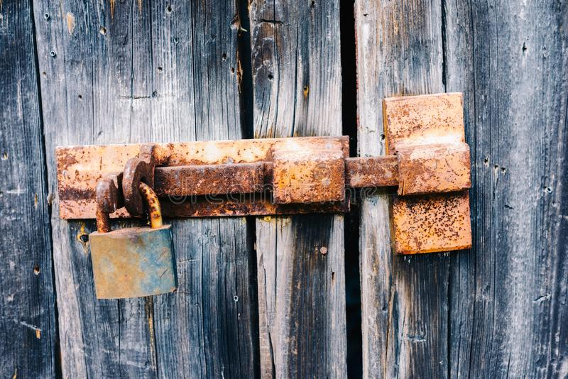 Old rusty latch with padlock on doors. Old rusty latch with padlock on wooden doors royalty free stock photos