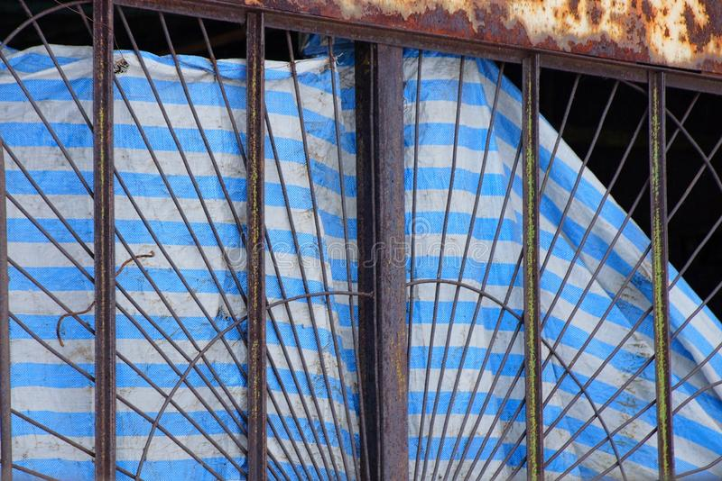 Old rusty lattice window with a striped curtain of torn fabric stock photos