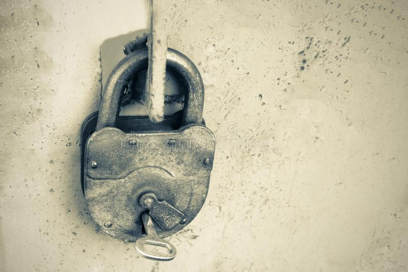 Old rusty lock with a key on a gray background, black and white photo.  royalty free stock photography