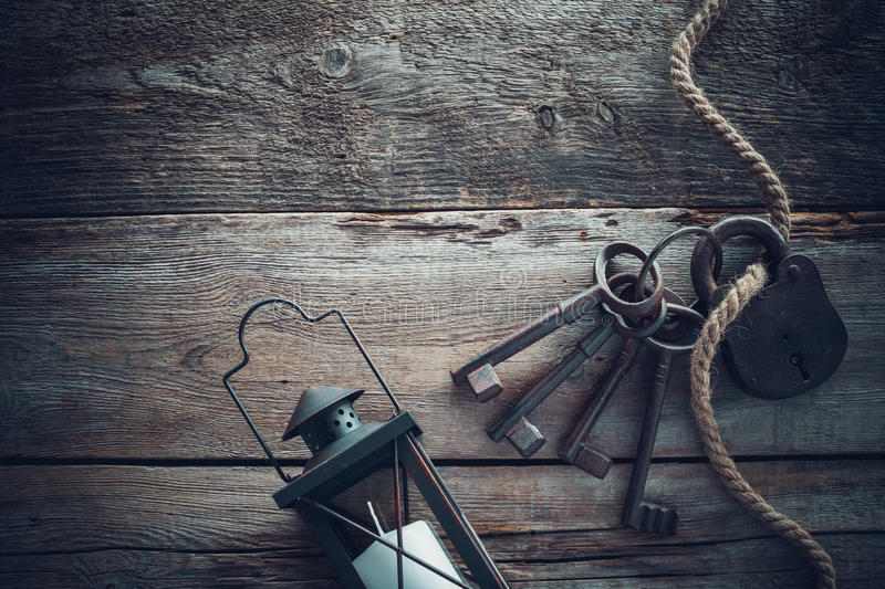 Old rusty lock with keys, vintage lamp, bottle and rope royalty free stock photography