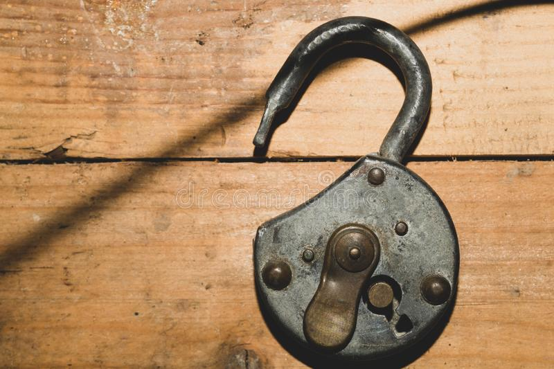 Old rusty lock on a wooden table. Vintage padlock on the wood background royalty free stock image