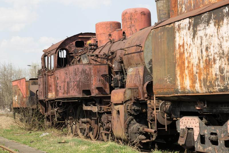 Old rusty locomotive stands on the rails on the background of blue sky.  royalty free stock photo