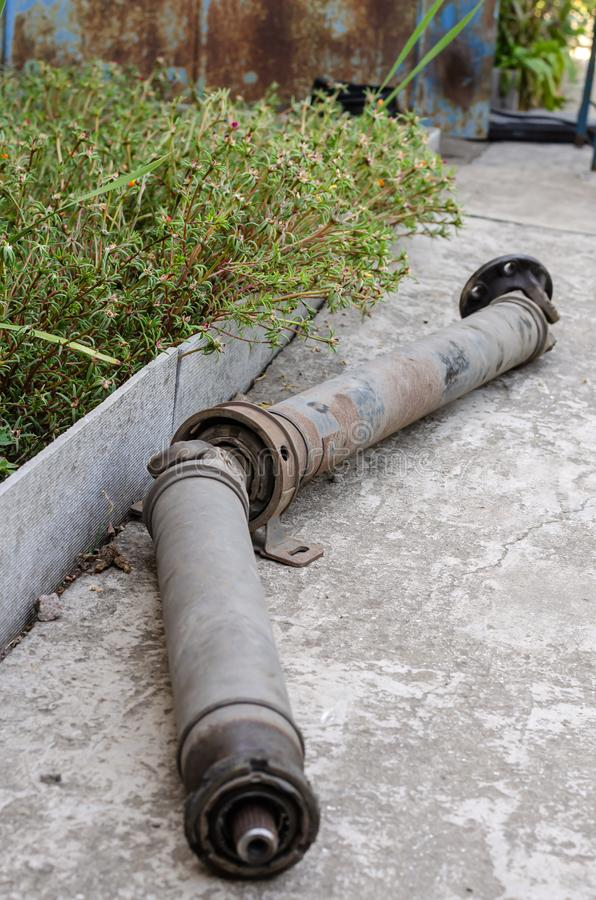 An old rusty long driveshaft lies on a concrete path in the courtyard of a rural house. Everyday life of rural life. Close-up. royalty free stock image