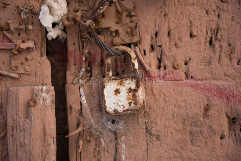 Old rusty metal closed lock on a brown doors. Vintage lock royalty free stock photography