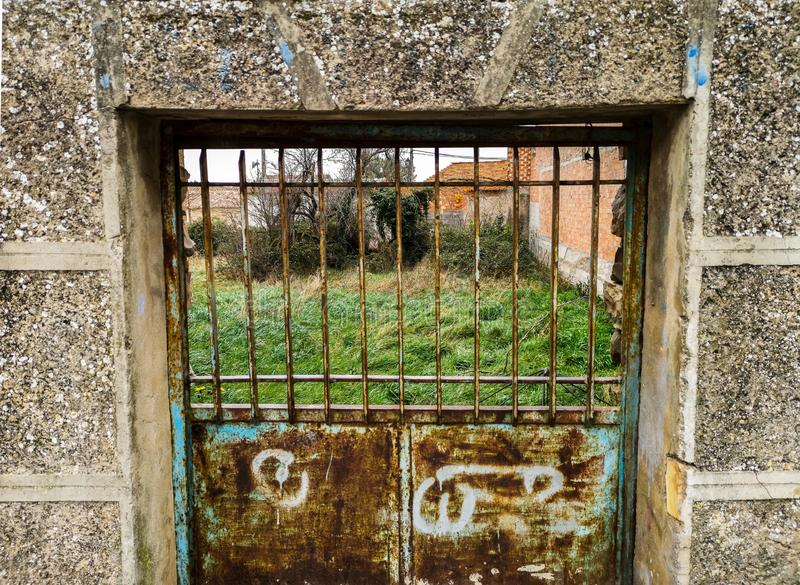 Old rusty metal door. In a stone wall ghetto green background locked boarded weathered doorway barred side mystery grunge backdoor backyard unprotected entrance royalty free stock photos