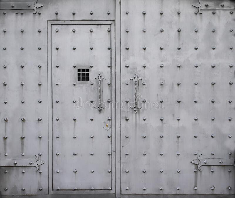 Old Rusty metal gate with door. Iron prison gate. Closeup prison gate background. Old Rusty metal gate with door. Iron prison gate. Closeup prison gate stock image