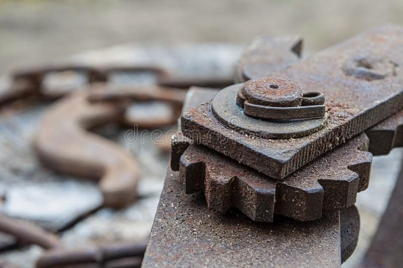 Old rusty metal gear. Fragment, detail. Lying on a cracked stump royalty free stock photography