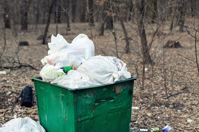 Old rusty metal green garbage container full with plastic waste standing in city park or forest. Environmental pollution stock photography