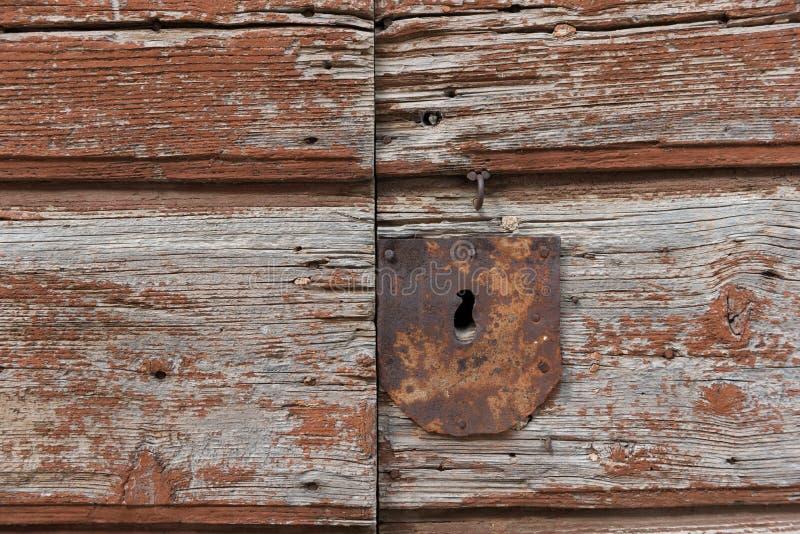 Old rusty metal keyhole on old brown wooden door. Rusty keyhole stock photos