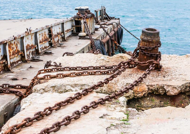 Old, rusty metal mounts and large chains for mooring in the seaport against. The background of the sea royalty free stock photos