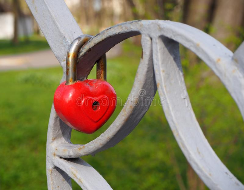 Old rusty metal red heart lock, the romantic symbol of never ending love hanging on the fence of bridge. Love forever through time stock photography