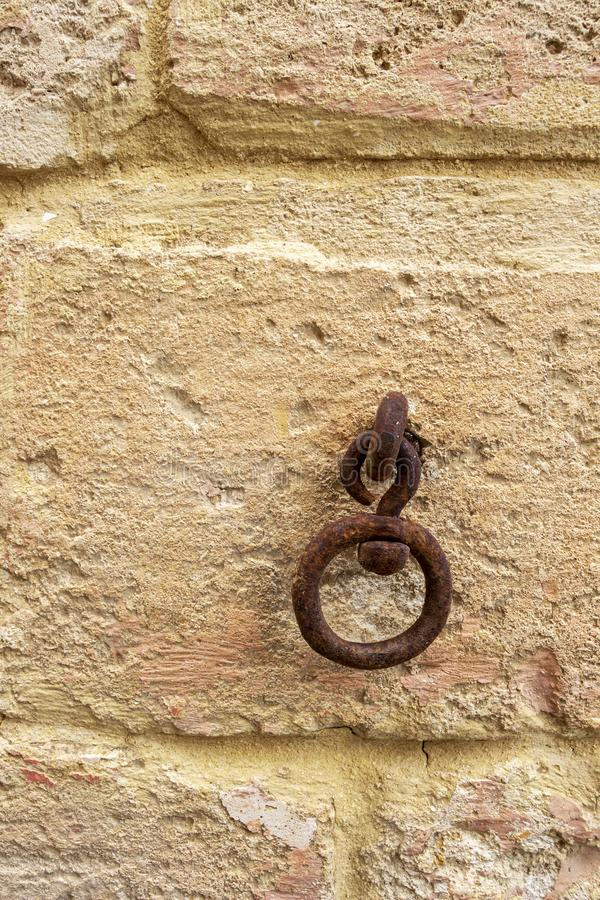 Old rusty metal ring on a limestone wall. Old rusty metal ring on a limestone building wall in Rabat, Malta, architectural detail royalty free stock photo