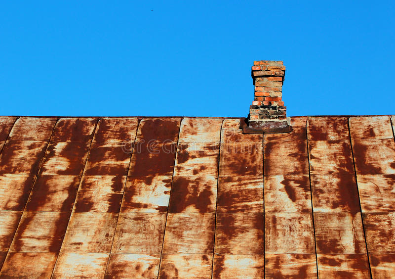 Old rusty metal roof with brick chimney against blue sky stock photography