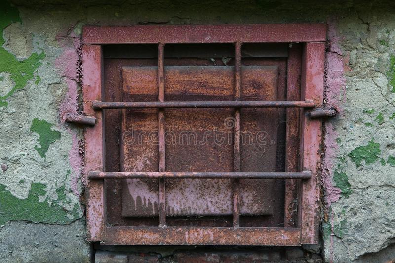 Old rusty metal window with grating on a peeling wall. Old rusty metal window with a grating on a peeling wall royalty free stock photography