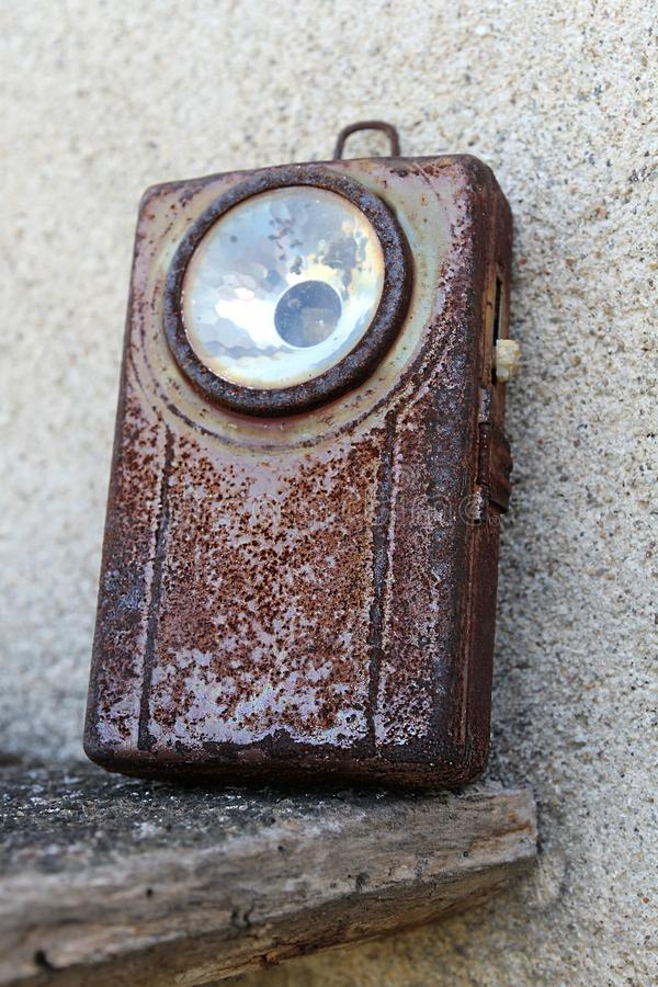 Old, rusty military pocket flashlight with preserved switch. An old, rusty pocket military flashlight. It was once olive green and it belonged to my grandfather royalty free stock photos