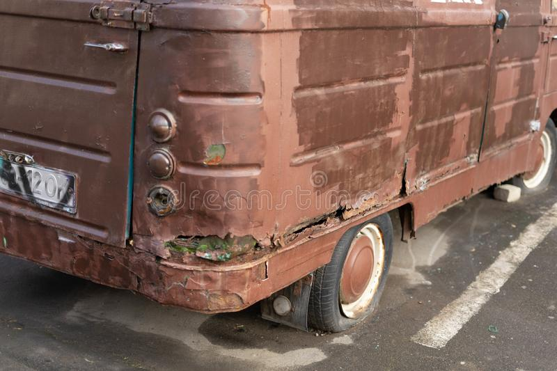 An old rusty minibus with a flat tire stands on a city street royalty free stock photos