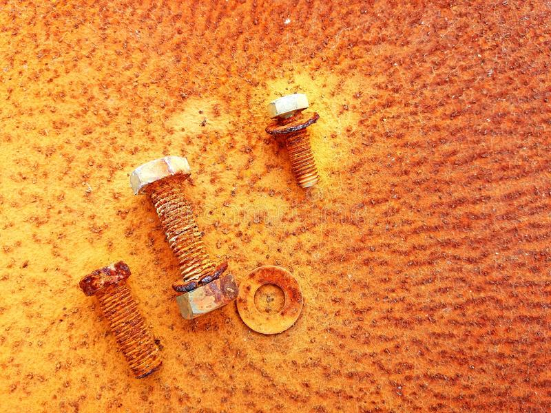 Old Rusty nuts, screws and bolts on rust steel background. royalty free stock photo