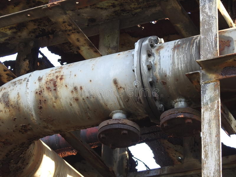 Old rusty oil pipes. Old oil pipes used to pump the oil from ship to refinery stock photos