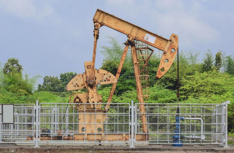 Old  rusty oil pump jack extracting crude oil and natural gas form well in green and cloudy oil fields of India, Asia. Oil pump jack mining for oil natural stock photography
