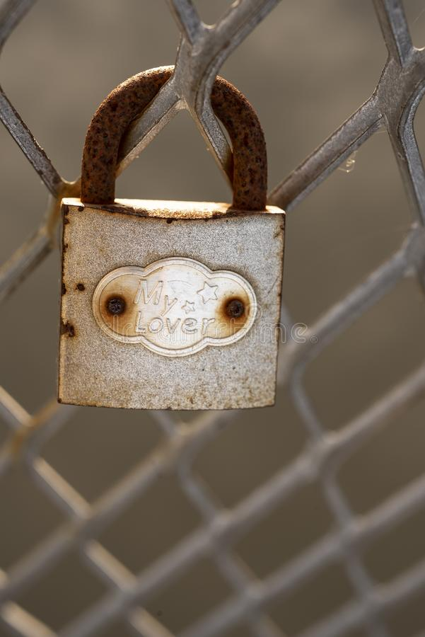 Old rusty padlock affixed on metal fence stock images