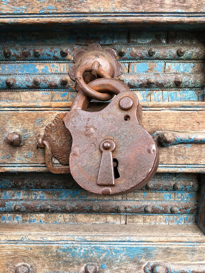 Old rusty padlock hanging on a dilapidated wooden door. Old rusty padlock in the closed position, hanging on a dilapidated wooden door, with iron ornaments and stock photos