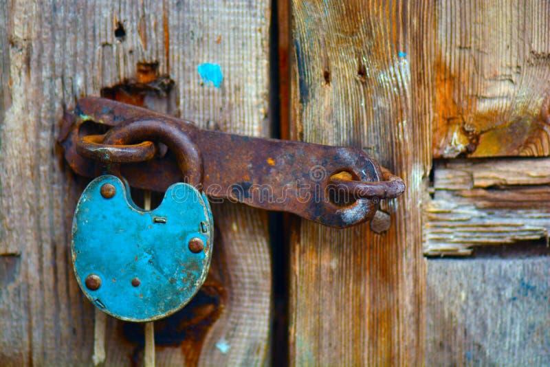 Old rusty padlock hanging on an old wooden door stock photo