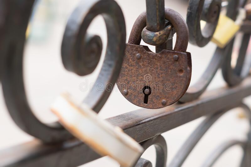 Old rusty Padlock on iron fence. Selective focus.  royalty free stock photo