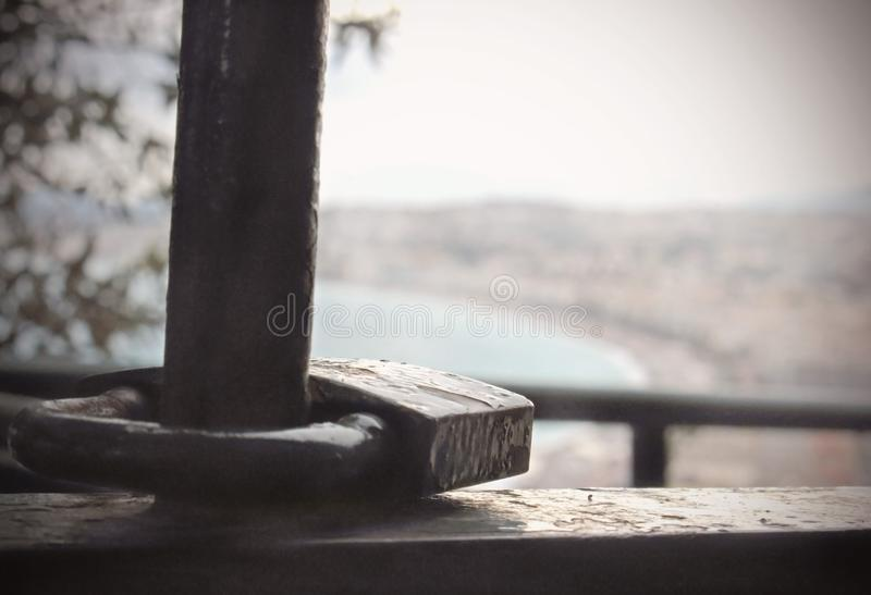 Old rusty padlock lying on a metal handrail on blurred background. Old rusty padlock lying on a handrail on blurred background, dull, blurry, haze, gray stock images