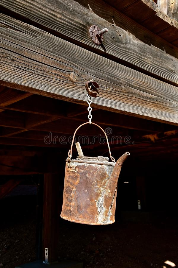 Old rusty pail hangs from a beam. A very old rusty can with a spout for pouring liquids hangs from a chain attached to a beam of an old mining structure royalty free stock photo